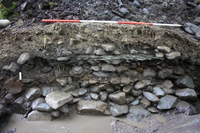 Figure 4. The hearth complex in section; the massive foundation slabs are visible at the base of the section, above which are the mounds of cobbles between hearthstones; at the base of the section to the left are the alder foundation timbers.